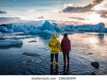 two people watching on floating icebergs in Jokulsarlon glacier lagoon in Iceland
