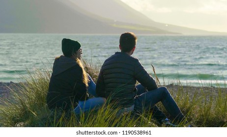 Two people at the waterfront sitting in reed grass