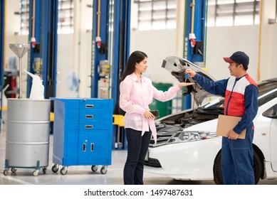 Two people when Monte Car in the car repair work for a beautiful young customer and the customers are happy in the service of the staff and are satisfied with the rep