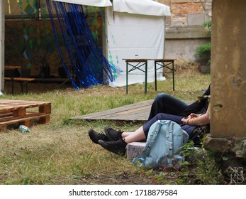 Two people who are sitting by the wall, we can only see their legs. Decorated tent in the background.