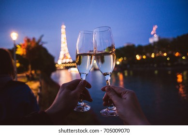Two people wining with champagne glasses in front of Eiffel tower in Paris. Couple cheering with champagne.