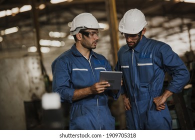 Two people working. Male Industrial Engineers Talk with Factory Worker while Using tablet.