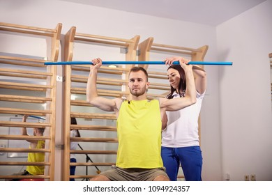 two people, working out, practising physiotherapist correcting, chekcing patient, upper body, back.
