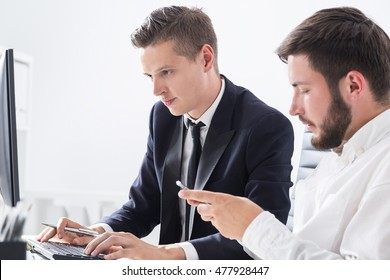 Two people working at task together. One businessman is checking details in internet. Second is looking at his smart phone screen. Concept of important project