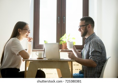 Two people working together on a project, talking and laughing, friendly relaxing atmosphere during negotiations. Man and woman brainstorm ideas for new startup, drinking coffee and working on laptops