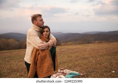 "two people, young couple, 20-29 years old. Man hugging woman behind her back. Lovely and romantic scene. In national park ""Fruska Gora"", Serbia, mountain hills, and yellow Autumn grass field."