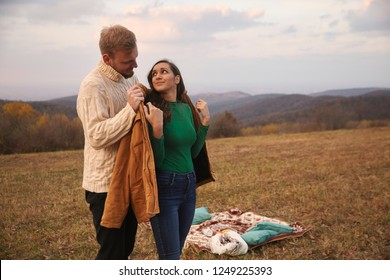 "two people, young couple, 20-29 years, lovely gesture gentleman putting his jacket on woman's back, standing behind her. picnic outdoors on mountain field, in national park ""Fruska Gora"", Serbia."