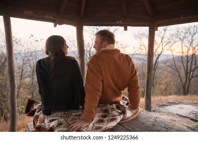 "two people, young couple or friends, siting on wood table and relaxing, talking and enjoying time outdoors. National park ""Fruska Gora"", Serbia."