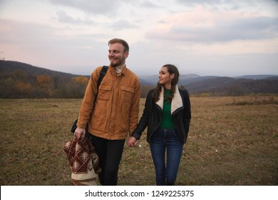 "two people, young couple holding hands, returning from picnic, walking on mountain hill in Autumn. Yellow grass field in rural area. Location ""Fruska Gora"", Serbia."