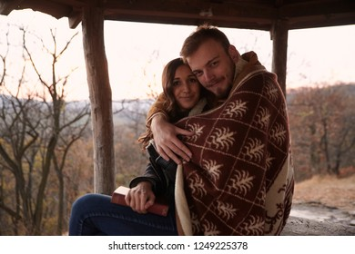 "two people, young couple, hugging under a blanket, in rural area. In national park ""Fruska Gora"", Serbia, sitting under a wooden, summer house, outdoors in Autumn."