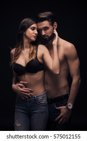 two people, young couple intimate woman hands touching man sexy, good looking, bra shirtless nude jeans, black background, dark