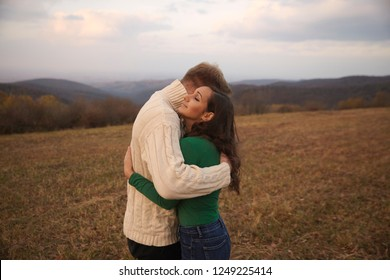two people, young couple, standing face to face and romantically hugging, 20-29 years old. Outdoors, mountain hill on Autumn yellow field, beautiful landscape behind in background.