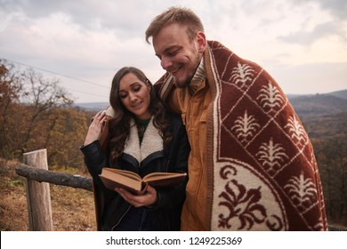 "two people, young couple, woman reading the book to a man, outdoors in nature, tucked under a blanket. Upper body shot, located in national park ""Fruska Gora"", Serbia."