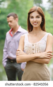 Two people: young smiling dark-haired woman wearing beige dress and young handsome man standing at summer green park.