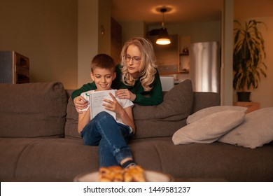 two people, young woman and boy, together happy, while doing homework in their living room.