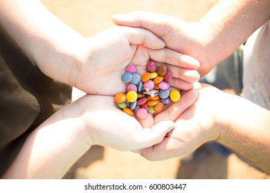 Two people's hands with smarties and an engagement ring.