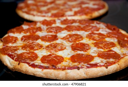 two pepperoni pizzas in a line on a black stove surface low angle