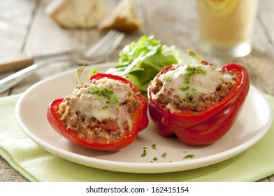 Two peppers stuffed with ground beef and topped with Parmesan cheese.