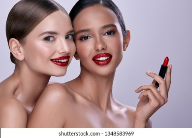 Two perfect girls with naked shoulders and perfect smiles posing with  red lipstick and smiling, wearing evening make up, portrait.