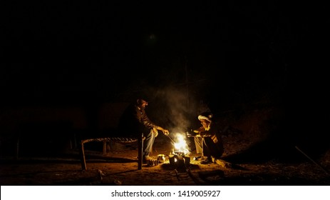 two person sitting near fire  Night shots of rural area  village Mahjori district Dhanbad Jharkhand state india clicked on 12march 2017