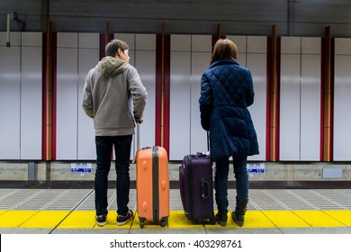 Two person are waiting a train subway at the train station