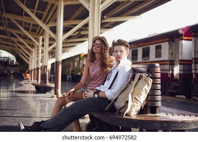 Two persone guy and girl travellers waiting for a train in asian train station