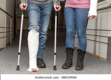 two persons with cast on on leg and arm, male is walking with crutches