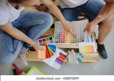 Two persons choose color of a decor, sitting on a floor. They show each other various options. Near them various catalogs with samples are spread out.