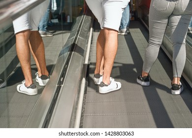 Two persons drive up an escalator, only the legs are visible, the left person is mirrored in the glass cover of the protective wall. A picture in delicate gray-white tones.