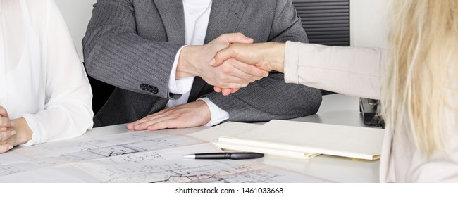 two persons and the female archtitect give handshake for agree on the office table with the constrtuction plans
