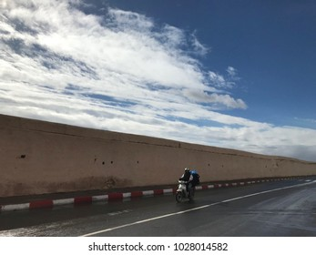 Two persons riding a moped on a lonely wall lined road with clouds in the background