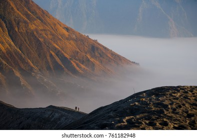Two persons seen from behind walk along the edge of a volcano crater in famous geologic formation Gunung Bromo, Java, Indonesia.