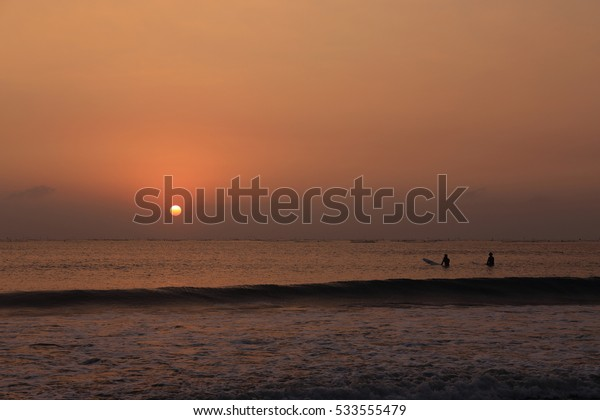 two persons surfing in the sunset beach in a winter evening
