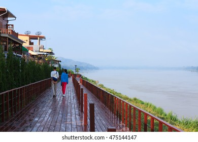 Two persons walk along a boardwalk of a small town named Chiang Khan which is next to Mekong river, Thailand.