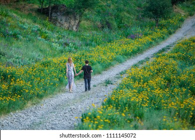 Two persons walk on country road with yellow flowers