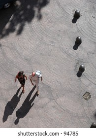 Two persons walking in the street, seen from a high standpoint