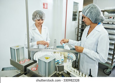 Two pharmaceutical factory workers at pharmacy industry manufacture checking medicine on conveyer