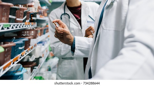 Two pharmacist looking for critical medicinal drug. Male doctor holding a medicine with female standing by in pharmacy.