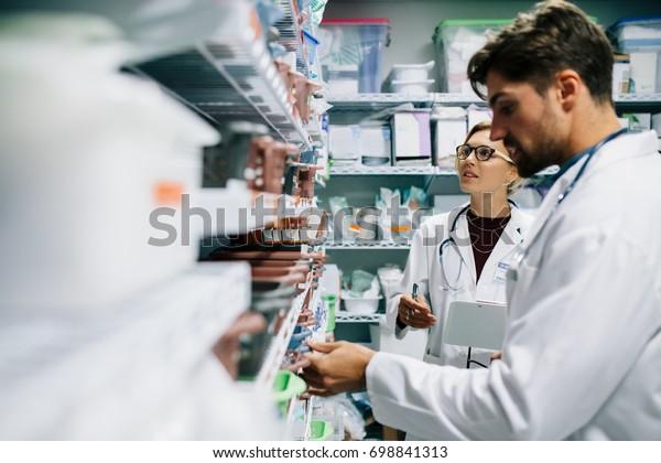 Due farmacisti che lavorano in farmacia. Farmacisti maschi e femmine che controllano l'inventario dei medicinali presso la farmacia ospedaliera.