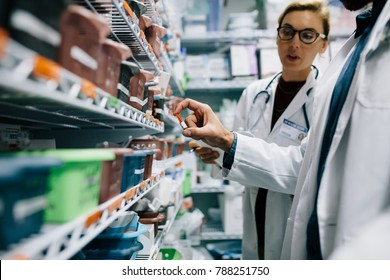 Two pharmacists checking inventory at hospital pharmacy. Hospital staff stocktaking in drugstore.