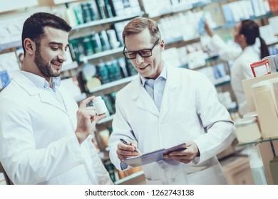 Two Pharmacists is Working. Pharmacists is Caucasian Adult Man and Young Guy. Guy Showing Bottle with Pills. Man is Writing Information about Medicine. People is Located in Pharmacy.