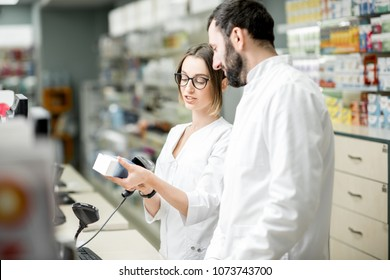 Two pharmacists working at the paydesk selling medications in the pharmacy store