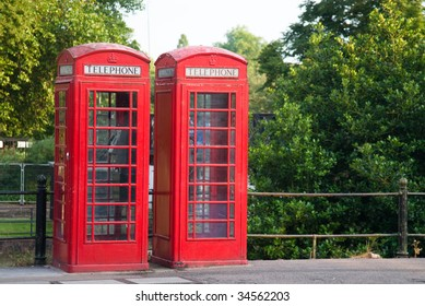 Two phone booths standing out against the green natural background