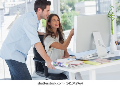 Two photo editors working on a computer in their office