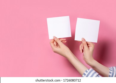 two photo frames on a pink background in the hands of a girl