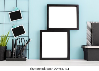 Two photo frames on a table with stationery, books and a plant. Mock up
