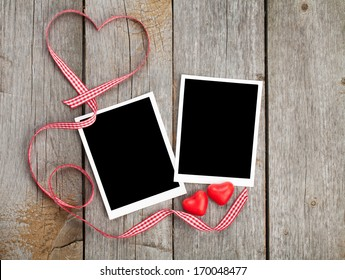 Two photo frames and small red candy heart on wooden background