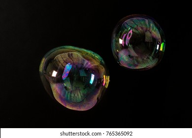 Two photographed giant irregular shaped soap bubbles on black background.