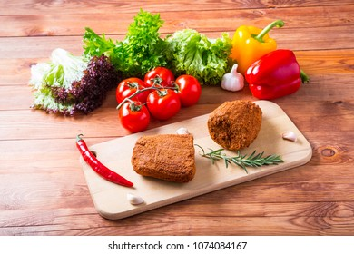 Two piece of bastirma and vegetables (salad, tomato, peper) on a wooden table