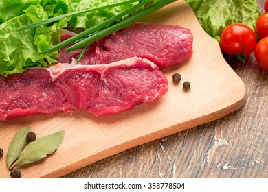 two piece of fresh,raw, juicy meat of veal or stake of beef,on a kitchen table on a wooden chopping board with  spices,black pepper,green lettuce leaves,ripe cherry tomatoes,fresh green onions,fennel